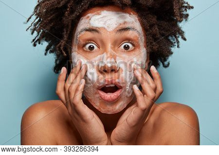 Natural Beauty Treatment Concept. Shocked Dark Skinned Woman Washes Skin, Has Soapy Face, Problems W