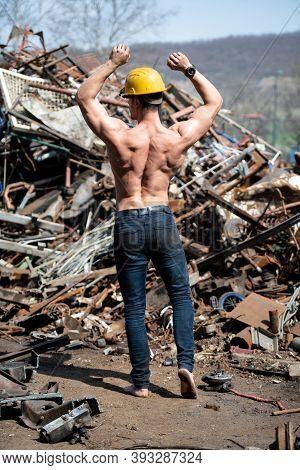 Muscular Bodybuilder Flexing Muscles In Industrial Junk Yard