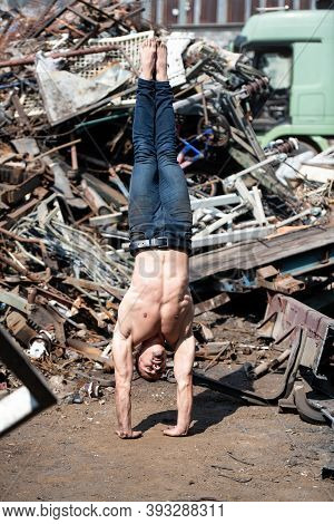 Young Athletic Man Doing Handstand At Industrial Junkyard