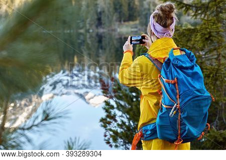 Image Of Young Hipster Girl Wears Yellow Anorak, Carries Tourist Rucksack, Makes Photo On Camera Of
