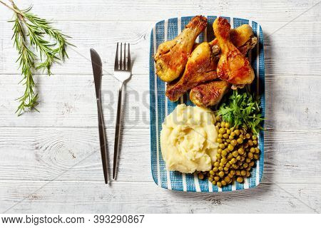 Easy Dinner: Baked Chicken Drumsticks Served On A Plate With Fresh Arugula, Mashed Potato, And Peas
