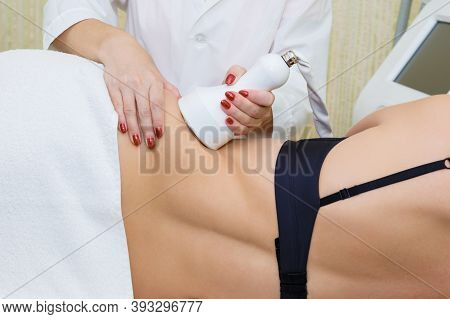 A Woman Beautician Makes A Cavitation Massage On The Side Of The Abdomen Of A Young Woman. Side View