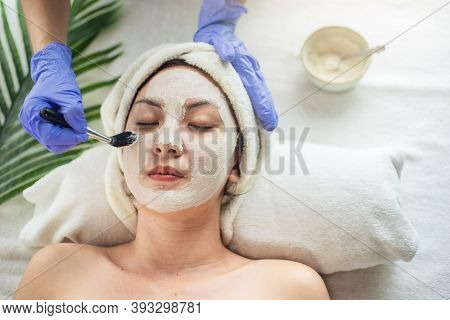 Asian Woman Getting Facial Face Care By Beautician At Spa Salon, Closeup Face Female Applying Clay M