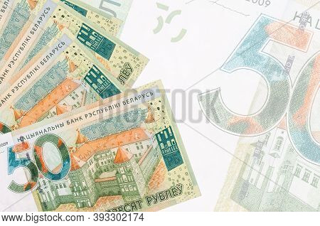 50 Belorussian Rubles Bills Lies In Stack On Background Of Big Semi-transparent Banknote. Abstract B