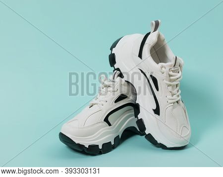 Black And White Sports Shoes On A Blue Background. Sports Shoes With High Soles.