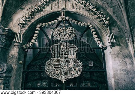 Kutna Hora, Czech Republic, May 14, 2019: Royal Coat Of Arms Made Of Human Bones And Skulls With Pil