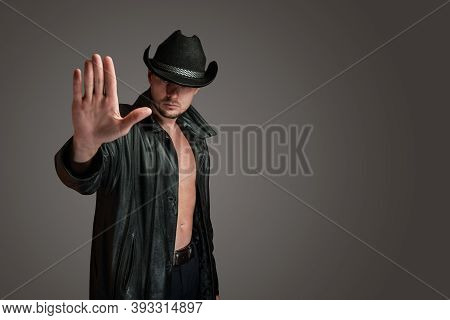 Cowboy In A Leather Coat Makes A Gesture Of Denial With His Hand. Unshaven Serious Man In Hat Isolat