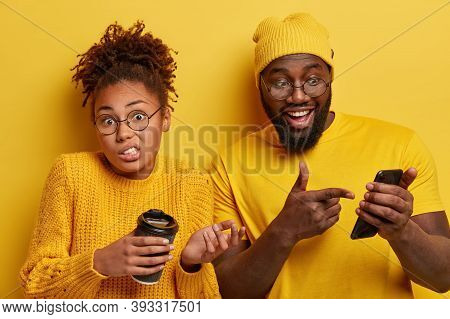 Glad Surprised Black Guy Points Into Screen Of Smartphone Device, Reads Funny Message Content, Puzzl