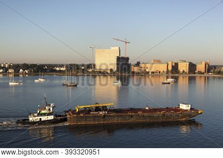 The Morning View Of A Tugboat Pushing The Platform And Norfolk City In A Background (west Virginia).