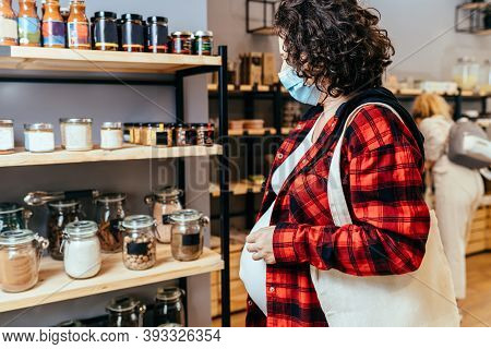 Pregnant Woman With A Cotton Shopping Bag Wearing A Protective Face Mask Choosing Foods In A Plastic