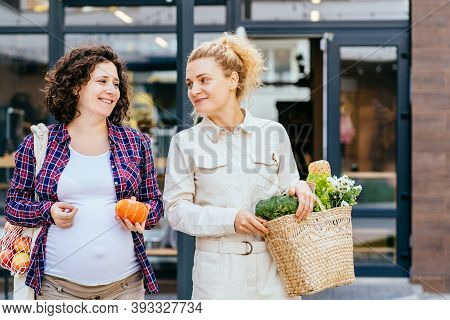 Pregnant Woman With Her Friend Discussing What To Cook, Sitting On Bench, After Shopping In Bulk Foo