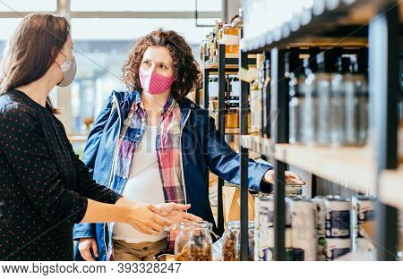 Shop Assistant Helping Customer In Bulk Food Store. Seller Advising Woman In Her Purchase Of Groceri