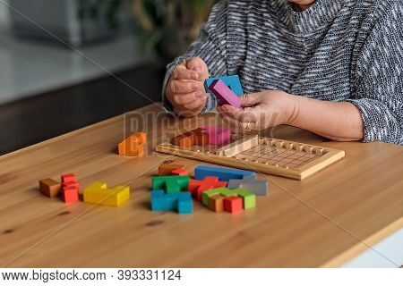 Activity Can Improve Brain Function. Elderly Woman Sitting At Table And Sorting Jigsaw Puzzle Pieces