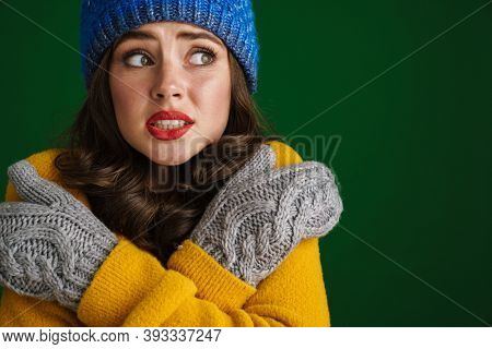 Beautiful unhappy girl in knit hat and mittens posing and trembling isolated over green background