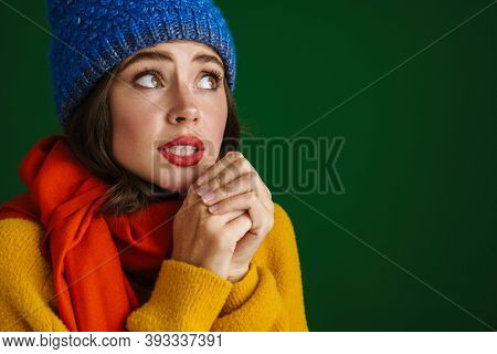 Beautiful unhappy girl in warm hat and scarf posing and trembling isolated over green background