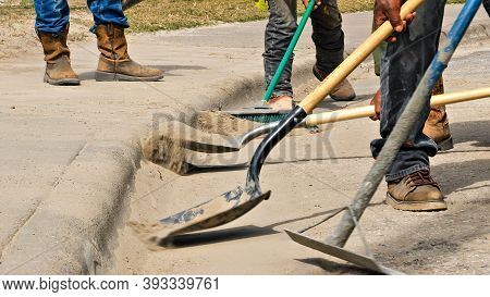 Construction Workers Use Shovels And Broom To Clean Dirt Off The Street By The Sidewalk At A Work Si