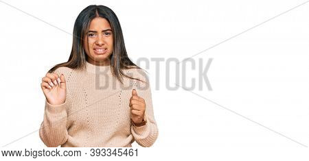 Young latin girl wearing wool winter sweater disgusted expression, displeased and fearful doing disgust face because aversion reaction.