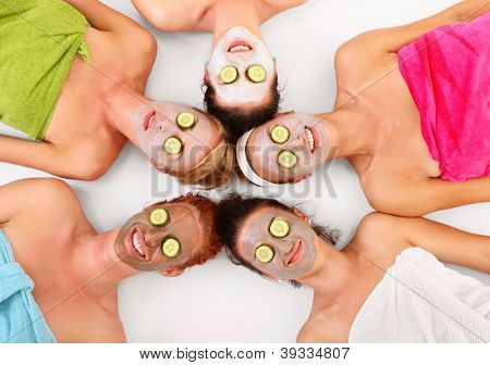 A picture of five girl friends relaxing with facial masks on over white background