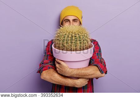 Photo Of Happy Young Male Flower Grower Embraces Big Pot With Prickly Cactus, Wears Stylish Hat And