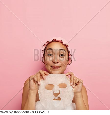 Pretty Satisfied Asian Girl Wears Shower Cap After Bath, Holds Paper Facial Mask, Has Spa Procedures