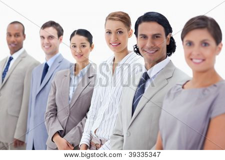 Close-up of smiling business people looking straight with focus on the two women in the middle