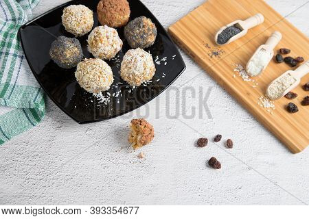 Home-made Energy Balls With Dried Fruits, Nuts, Sesame Seeds, Cocoa, Almonds And Poppy Seeds On A Bl