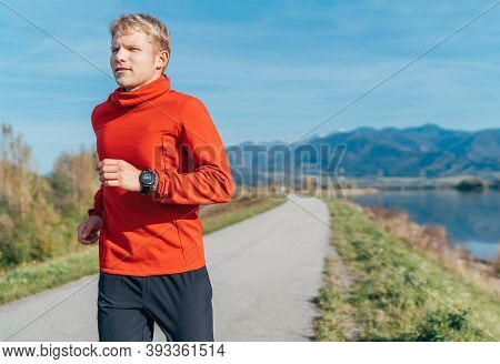 A Man Dressed In Red Long Sleeve Shirt Have A Morning Jogging By The Road With A Mountain Background