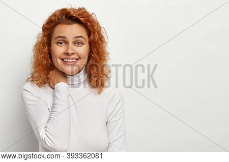 Studio Portrait Of Happy Redhead Curly Woman Feels Enthusiastic And Amused, Touches Neck Gently, Smi