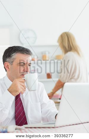 Man drinking coffee while checking laptop in kitchen before work
