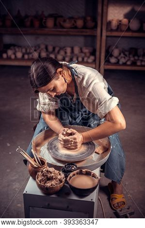 Charming Pottery Woman Making Ceramic Pot On The Pottery Wheel . Pottery Workshop.