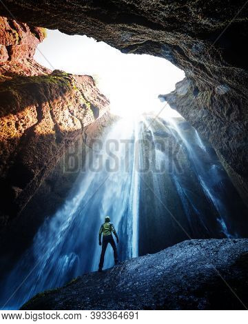 Man in the cave near the Gljufrabui waterfall, Iceland, Europe. Landscape photography