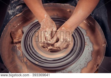 Hands Of The Master Potter And Vase Of Clay On The Potters Wheel Close-up. Master Crock. Twisted Pot