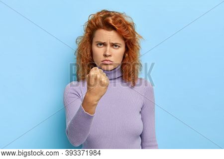 Fierce Displeased Serious Redhead Girl Shows Clenched Fist With Anger, Being Ready For Any Challenge