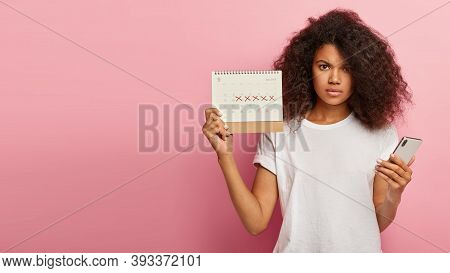Displeased Dark Skinned Woman Has Unhappy Look, Holds Periods Calendar With Marked Critical Days, Mo