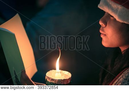 A Children Singer Hands Holding Candle And Book With Singing Carol Song On Celebration Of Christmas