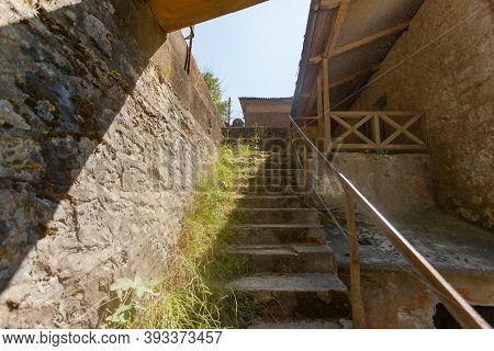 An Old Stone Staircase Along The Steep Wall With Grass Along A Steep Wall On A Sunny Day, On The Rig