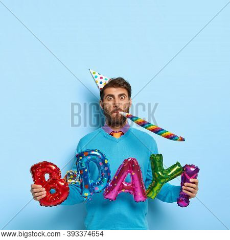Funny Caucasian Male Blows In Party Horn, Holds Letter Shaped Balloons Meaning Birthday, Wears Festi