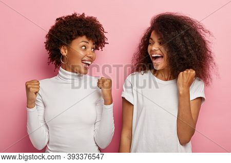 Photo Of Joyous Women Look At Each Other, Raise Clenched Fists With Triumph, Show Victory Gesture, L