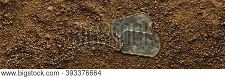Lost US military soldier's dog tags, rough and worn with blank space for text, covered in dirt. Memorial Day or Veterans Day concept.
