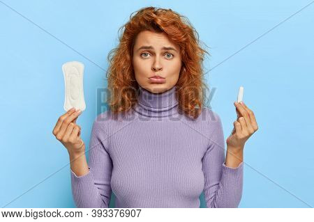 Upset Redhead Woman Holds Hygienic Sanitary Pad And Tampon, Chooses Good Protection During Red Days,