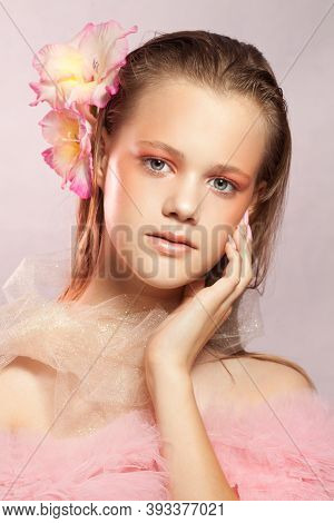 Young Beautiful Woman With Perfect Skin And A Flower In Her Hair On Pink Background
