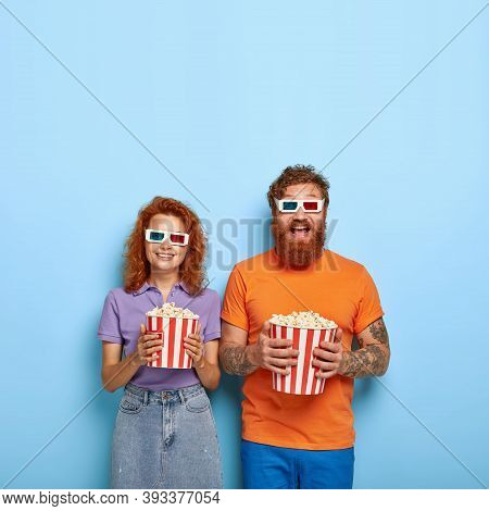 Studio Shot Of Amused Happy Red Haired Boyfriend And Girlfriend Entertained In Cinema, Wear 3d Glass