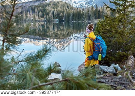 Outdoor Shot Of Young Traveler With Bag, Stands Back To Camera, Enjoys Mountains, Fresh Air And Smal