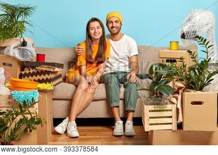 Our First Home. Newlywed Couple Bring Boxes With Belongings In New Apartment, Hug And Sit On Sofa, S