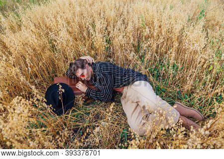 Tall Handsome Man With Brown Suitcase Full Of Ears Of Oats Laying At Golden Oat Field.