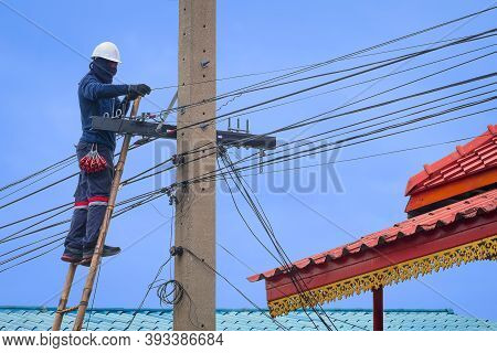Asian Technician On Wooden Ladder Is Installing Cable Lines To Connect Telephone And Internet Signal