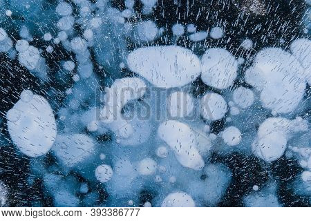 Beautiful Transparent Blue Ice With Frozen White Methane Bubbles. Winter Structure Of Frozen Lake Ba