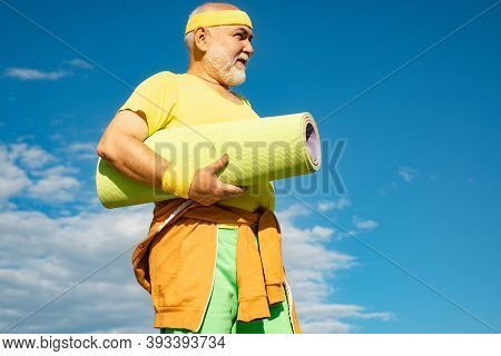 Cheerful Aged Men Holding Yoga Mats. Grandfather Pensioner. Elderly Man After Her Workout. Fit Senio