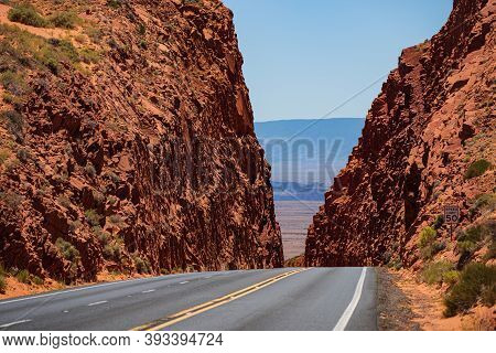 Road Against The High Red Rocks. Barren Scenery, Endless Straight