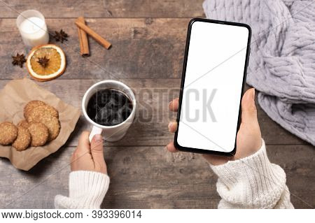 Mock-up Mobile Phone. Woman At A Wooden Rustic Table Drinks Coffee And Looks At A Mock-up Mobile Pho